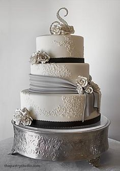 this beautiful cake features a soft grey sash and accents of black with sugar-paste roses.