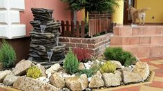 Gardening do it yourself. garden fountain with mountain rocks and plants.