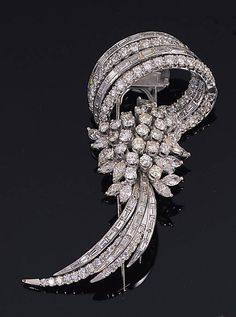 A DIAMOND CLIP BROOCH Set with a cluster of circular and marquise-cut diamonds, with a baguette and circular-cut diamond spray terminal, enhanced by a swirl of baguette and circular-cut diamond scrolls, 7.2cm. high