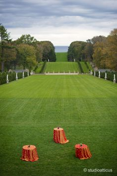 orange tablecloths on high top tables contrast nicely with the green lawn and evening light. Crane Estate wedding in Ipswich, MA.