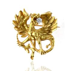 Gold and diamond dragon brooch, the roaring dragon with wings spread holding an old mine-cut diamond in his jaws