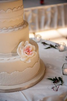 White and cream wedding cake, lace detail and floral accents.