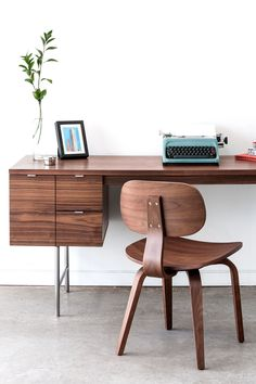 The Conrad Desk is a compact home office desk with a strong Mid-Century pedigree. All surfaces are finished in walnut, to contrast the slender, tubular stainless steel legs and brushed aluminum drawer pulls. The main drawer is designed to hold hanging file folders, and the two smaller drawers are perfect for organizing stationary and supplies. This desk evokes the style of 1950s Modernism, but with a scale and functionality suited perfectly for today. Modern Home Offices, Modern Office Design, Modern Desk, Home Office Desks, Stationary Organization, Hanging File Folders, Hanging Files, Small Drawers, Walnut Finish