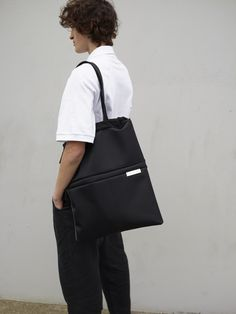 """Made from black 100% Nylon with a silky feel, this hybrid between laptop sleeve and clutch bag transforms into a large carrying volume, to be used as a shopper when needed. Suitable for laptops of up to 15"""", the ZAAN can be used to transport just the essential tools to the office. In tote format it is ideal for carrying additional items. Sling Backpack, Leather Backpack, Black Tote, Laptop Sleeves, Clutch Bag, Laptops, Backpacks, Tools, Diy"""