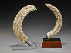 "Two Antique African Carved Ivory Hippos' Tusks Two very elaborately carved, antique African ivory hippos' tusks: each with many figures continuously scrolling the full length, some in Western clothes; L: 15"" (longer, along outer curve)"
