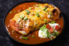 These beef and bean wet burritos are smothered with red sauce and melted cheese. Top with your favorites such as guacamole, sour cream, lettuce, onion, and tomatoes. We often are requested to make these when company comes over. If your cooking for two, you can freeze the leftovers. To reheat - allow to thaw completely first then preheat your oven to 400 degrees F (200 C) and bake for 20 - 25 minutes until heated through.