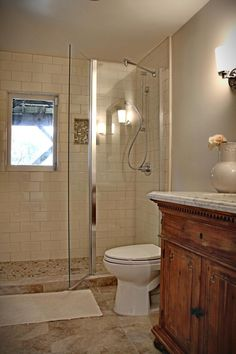 A detailed wood vanity brings Mediterranean elegance to this petite neutral bathroom offering luxurious amenities such as a glass walk-in shower and marble floor.