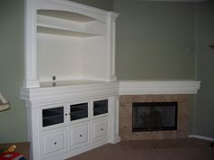 entertainment builtin with corner fireplace - mantle trim continues through the entertainment center