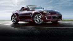 2016 Nissan 370Z Roadster Touring shown in Black Cherry from side angle view, blue sky in background