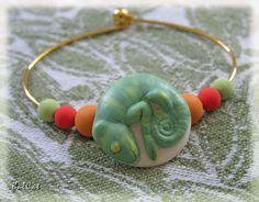 BraceletEnfant01 Bouton fève, en biscuit peint représentant un caméléon... vert, et appartenant à une collection d'annimaux. Il est enfilé (bloqué) sur un jonc en métal doré et encadré de perles de couleur. Création BalCat