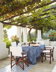 At a magical Italian island villa perched above the sea, owned by the founders of Dedar, the terrace has a floor of cement and Sicilian tiles and a pergola with climbing grape vines.