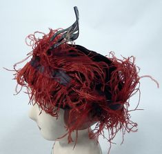 Vintage McGrath Millinery Belle Epoque Burgundy Velvet Feather Trim Toque Hat The hat is made of a dark red burgundy wine color velvet fabric, with reddish orange ostrich feathers and gold lamé ribbon trim surrounding it.
