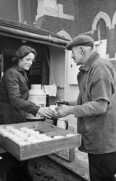 Rachel Bingham serves tea from the back of her WVS tea car to a man who has been helping to clear up the rubble and debris caused by an air raid in this area of London, 1941.