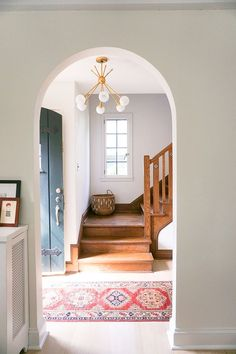 modern gold light fixture in the entryway || vintage rug