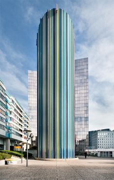 Paris, France - This tower in La Defense business district is called Cheminee d'Aeration by Raymond Moretti. The tower sculpture is nearly 100 feet high and comprised of concrete and fiberglass. There are apparently 700 narrow, colorful fiberglass tubes surrounding the tower. Not an office building at all - apparently art hiding a ventilation shaft.
