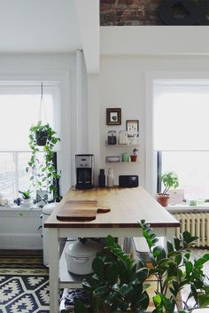 Kitchen island + coffee station. | White kitchen with wood counters and lots of plants and bold pattern rug.