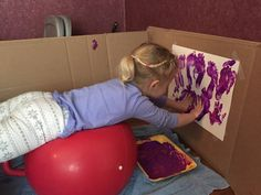 This activity allows children to paint while promoting postural praxis because the child has to plan how they are going to paint while being balanced on a ball.