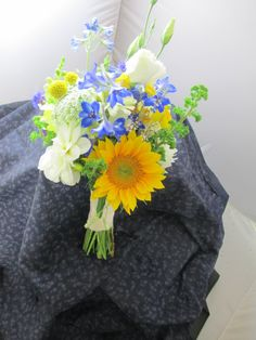 Bright, summery bridal bouquet in yellow, blue, and white. Sunflowers, delphinium, lisianthus. Tied off in ivory ribbon. Maine destination wedding. Late August.