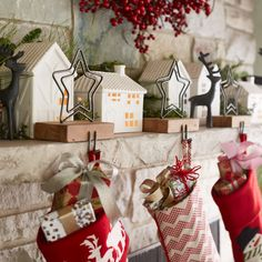 White porcelain tudors light up a cozy winter village with old-world charm. The stars come out as stocking holders in antiqued zinc on recycled wood. Handcrafted deer take in the scene beneath a twig wreath ringed in faux holly berries bright with holiday color.