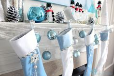 Furniture and Accessories. Cute snowy Christmas fireplace mantel decoration in white and blue with cool snowman ornaments, shiny balls, snow...