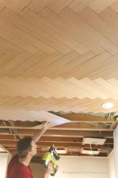 Can you believe this is actually a BUDGET ceiling?! This herringbone ceiling looks expensive. If you're looking for basement ceiling ideas we've got another here for you. This is a plywood ceiling and we've got the simple tutorial. Could be used to cover popcorn ceilings too! Part of our budget basement makeover. #howto #DIY #decor #ceiling #basement #basementideas #budgetdecor