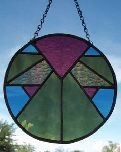 Round geometric design in olive green, steel blue and plum - such a pretty piece!    Measures approximately 8 in diameter, this stained glass