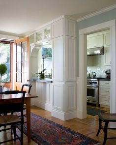 An arched surround lends a graceful note to this pass-through and offsets the boxiness of the cabinetry that frames it..