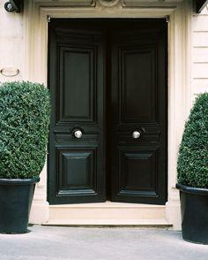 love the dark doors, limestone, and evergreens - perfect balance