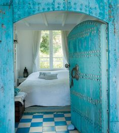 blue painted door in a blue wall with blue and white tile floor ..... leading to a glorious bedroom