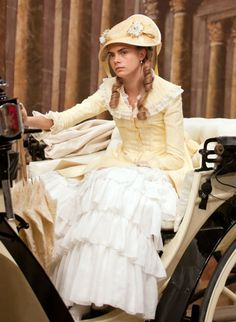 Anna Karenina - Cara Delevingne as Princess Sorokina wearing a pale yellow corseted dress with ruffled white skirt and lace details on the bodice. A lace parasol and a straw hat with ribbons and flowers complete the outfit. Cara Delevingne, Anna Karenina, Period Costumes, Movie Costumes, Lace Parasol, Georgia May Jagger, Victorian Gown, Fantasy Gowns, Vintage Mode