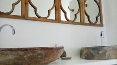White resin walls and natural stone sinks look great in our master bathroom combined with wooden fleamarket mirrors and cow horns mounted on the wall as towel hooks (just visible in the mirror reflection)