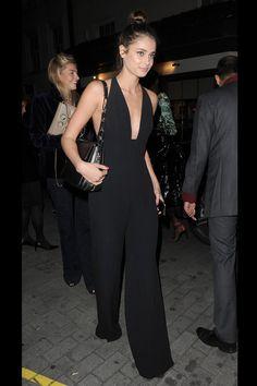 Taylor Hill en la fiesta de Business of Fashion. Con mono negro con pantalón palazzo y amplio escote en V y bandolera corta negra.