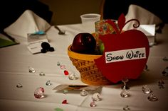 """Table #19: Snow White.  For Snow White we placed a basket of green apples on the table with a single red """"poison"""" apple. We used a glass votive with """"submersible"""" LED lights and Aquagems for lighting. Both the Aquagems and the princess jewels that we used for scatter were Snow's colors … red, blue, and yellow. The table marker was a bitten apple. I apologize because the """"reference photo"""" had not been taken off of the table yet at the time this picture was taken!"""