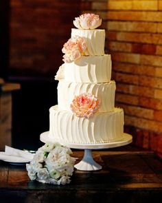 A four-tier buttercream cake with a pop of color from pink posies