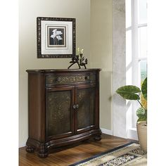 <li>Chest brings beauty and function to your living room<li>Furniture is constructed of hardwood and MDF with a deep brown stained finish<li>Living room furniture features a faux hammered metal front to create scroll and flower accents