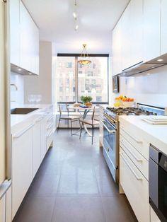 Cocina pequeña larga y estrecha con gabinetes color blanco con comedor de diario.