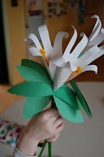 """Trace your hand on white paper and cut out.Take  short length orange pipe cleaner,twist it to the end of a long green pipe cleaner so the ens stick up like a """"V"""" with droopy ears. This is flower's center.      Wrap the hand print around the top of the green pipe cleaner and tape      Poke hole in middle of  double leaves & thread onto  pipe cleaner       Wrap tape around stem below the leaves"""