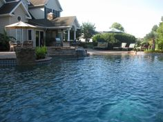 A relaxing, custom concrete pool with all the options! waterfalls, hot tub, beach entrance, outdoor kithchen, and more!