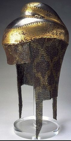 Indian helmet with chain mail neckguard, approx. 1820-1840. Probably Lahore, Punjab province. Helmet of iron overlaid with gold; mail neckguard of iron and brass.