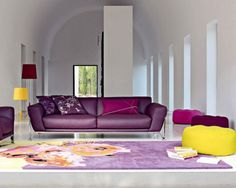 Charming Living Room Designs with White Wall Paint Color and Purple Carpet Floor and Colorful Round Shaped Ottoman Set and Single Purple Leather Sofa plus Yellow Red Drum Shaped Floor Lamps