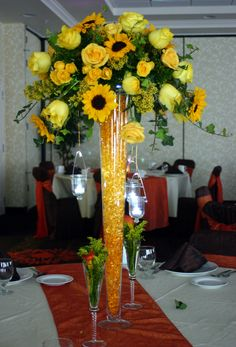 Wedding Countdown A monochromatic centerpiece features sunflowers, roses, and hanging votives in our tall pilsner vase. Sunflower Centerpieces, Sunflower Arrangements, Blue Centerpieces, Tall Wedding Centerpieces, Wedding Table Decorations, Decoration Table, Table Arrangements, Centrepieces, Outdoor Wedding Tables