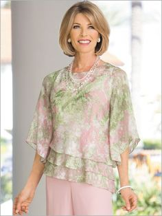 The ultimate in formal flattery. This rare and refi ned top creates a slender silhouette with a triple-tiered hem that is cut at an angle. Designed in an airy chiffon. Floral print is romanced in a palette of pastels Blouse Styles, Blouse Designs, Wedding Pantsuit, Dress Outfits, Fashion Dresses, Clothes For Women Over 50, Tiered Tops, Alex Evenings, Beautiful Blouses