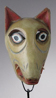 Dog mask  Uruapan, Michoacan    10 inches long, painted wood, animal teeth    Masks from Uruapan are often painted with a kind of lacquer, as is this one. The pale slightly greenish color and the eery eyes give this weird doggy a ghost-like appearance.