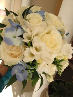 Fresh white freesia's, fragrant garden roses, china like tea roses, and a touch of silk blue hydrangea set off this hand tied bridal boquet for a midweek, sunset wedding in March ..  Designed by Nadine