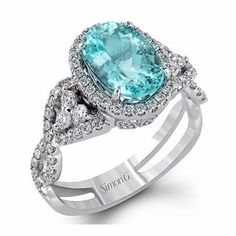 This extraordinary Simon G antique style 18k white gold ring, features round brilliant cut white diamonds of G-H color, SI1 clarity, weighing .70 carat total, with a beautiful center oval cut paraiba tourmaline.