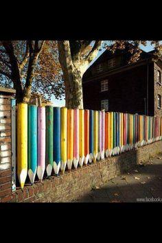 cette clôture est une clôture de l'école. Il est fait de bois. C'est crayons. Elles sont lumineuses et colorées. Les couleurs sont jaune, bleu, vert, rouge, violet et orange.