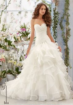 """Wedding Gowns By Blu featuring Asymmetrically Draped and Flounced Organza Gown Available in Three Lengths: 55"""", 58"""", 61"""". Colors available: White, Ivory, Blush."""