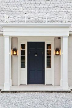 Beautiful home exterior boasts a navy front door flanked by sidelights illuminated by carriage lantern wall sconces.