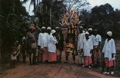 """""""An Onitsha Ijele, its headdress displaying """"eyes"""" and snake and, below, the masked visage of the ancestral figure, escorted by members of its appropriate age-set. """" Richard N. Henderson and Ifekandu..."""