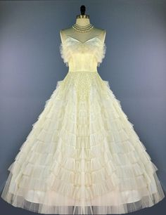 We are pleased to offer this yummy cupcake confection prom or wedding dress from the 1950's. This is a Cotillion Original.  FABRIC: This is made of off-white/ivory soft nylon net tulle. The waist is detailed with ivory vanilla (not yellow...there is no yellow in this dress) ) floral lace. Lined in ivory acetate.  This strapless beauty features a fitted boned shelf-bust bodice with a sweetheart neckline and ruffled trim. This has a voluminous full circle skirt with 2 layers of tires ...